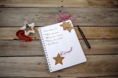 有圣诞节购物清单的笔记本 库存图片