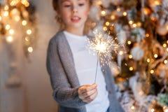有圣诞节闪烁发光物的女孩 免版税库存图片