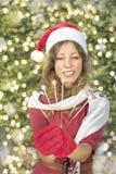 有圣诞节闪烁发光物的美丽的圣诞老人女孩 库存照片