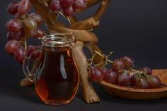 有在一个美丽的古色古香的碗的葡萄围拢的葡萄饮料的玻璃水罐果子的 库存图片