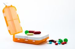 有在与拷贝空间的白色背景隔绝的五颜六色的胶囊药片的橙色药片箱子 免版税图库摄影