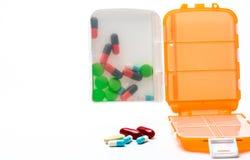 有在与拷贝空间的白色背景隔绝的五颜六色的胶囊药片的橙色药片箱子 库存图片