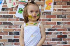 有在五颜六色的油漆绘的面孔的美丽的矮小的微笑的女婴 库存图片