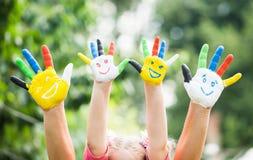 有在五颜六色的油漆绘的微笑的色的手 免版税库存照片