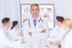 有在会议室横渡的胳膊的医生 免版税库存照片