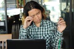 有在办公室被超载的膝上型计算机的疲乏的劳累过度的年轻亚裔人 免版税库存照片
