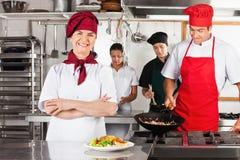 有在厨房里横渡的胳膊的女性厨师 免版税库存图片