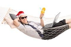 有在吊床的圣诞老人帽子的年轻人 免版税库存照片