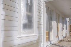 有在塑料盖的窗口的未完成的家 库存图片
