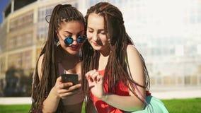 有在夏天公园畏惧的愉快的妇女坐草和使用智能手机 观看年轻的朋友谈话和 股票录像