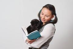 有在她的胳膊读书的一只滑稽的猫的逗人喜爱的少女女学生 特写镜头 免版税库存照片