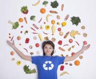 有在她的头被伸出的和新鲜的水果和蔬菜胳膊的微笑的少妇,演播室射击附近 图库摄影