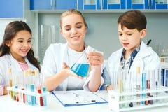有在学校实验室解释题目的老师的小孩 免版税库存图片