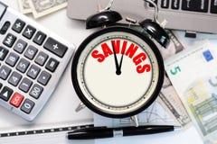 """有在它的显示写的词""""savings†的一个减速火箭的闹钟建议的随着时间的推移储款概念 库存照片"""