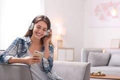 有在家休息在扶手椅子的耳机和移动设备的年轻女人 免版税库存图片