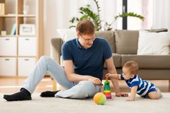 有在家使用一点小的儿子的愉快的父亲 免版税库存照片