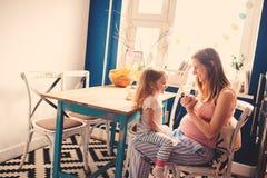 有在家使用她的小孩的女儿的愉快的孕妇 免版税库存照片