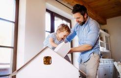 有在家使用小的女儿的成熟父亲户内 免版税图库摄影