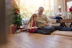 有在家使用数字式片剂的祖父的小女孩在期间 免版税库存照片