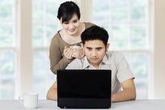 有在家使用膝上型计算机的女孩的人 免版税图库摄影