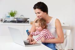 有在家使用膝上型计算机的孩子的母亲 免版税图库摄影