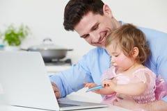 有在家使用膝上型计算机的孩子的父亲 免版税库存图片