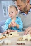 有在家使用他的男婴的父亲 库存照片