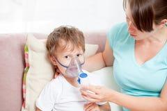 有在家做与雾化器的儿子的年轻女人吸入 库存图片