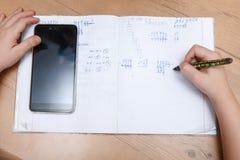 有在家做家庭作业的智能手机的男小学生 免版税库存照片