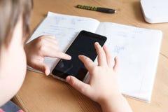 有在家做家庭作业的智能手机的男小学生 免版税图库摄影