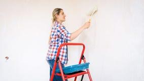 有在家做整修的漆滚筒的美丽的微笑的少妇 免版税库存图片