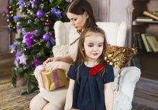 有在家包裹圣诞节礼物的女儿的愉快的母亲 免版税库存图片