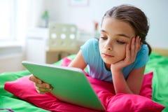 有在家在床上的片剂个人计算机的微笑的女孩 免版税库存图片
