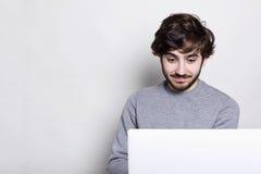 有在家坐在他的便携式计算机前面的现代发型的一个惊奇的有胡子的行家使用Wi-Fi,看起来惊奇 嗡嗡声 图库摄影