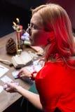 有在家实践的波浪发的金发的占卜者坐在桌上 免版税库存图片