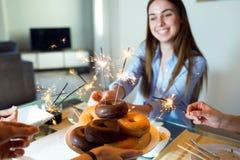 有在家庆祝她的生日的朋友的美丽的愉快的少妇 免版税库存照片