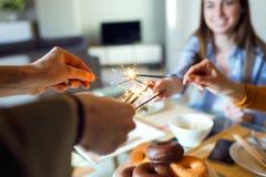 有在家庆祝她的生日的朋友的美丽的愉快的少妇 库存照片