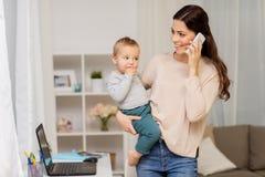 有在家拜访智能手机的婴孩的母亲 免版税库存照片