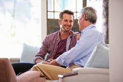 有在家放松在沙发的成人儿子的资深父亲 免版税库存照片