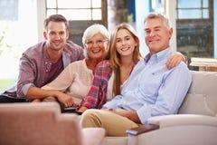 有在家放松在沙发的成人孩子的家庭一起 免版税图库摄影
