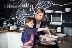 有在家烹调她的母亲的一个小女孩 免版税库存照片