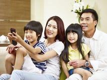有在家看电视的两个孩子的亚洲家庭 免版税库存图片