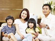 有在家看电视的两个孩子的亚洲家庭 库存图片