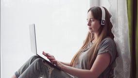 有在家研究膝上型计算机的耳机的妇女 影视素材