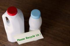 有在家站立在木桌上的纸贴纸的塑料瓶在白天 免版税图库摄影