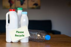 有在家站立在木桌上的纸贴纸的塑料瓶在白天 库存照片