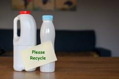 有在家站立在木桌上的纸贴纸的塑料瓶在白天 免版税库存照片