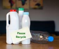 有在家站立在木桌上的纸贴纸的塑料瓶在白天 免版税库存图片