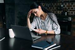 有在家计数税的计算器和膝上型计算机的沮丧的年轻女人 免版税库存照片