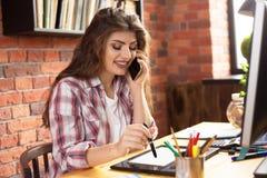 有在家运转与图形输入板或在顶楼样式办公室的长发的年轻女性 她谈话在电话和 免版税库存照片